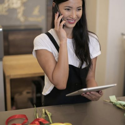 positive-ethnic-businesswoman-using-gadgets-at-own-floral-3932728