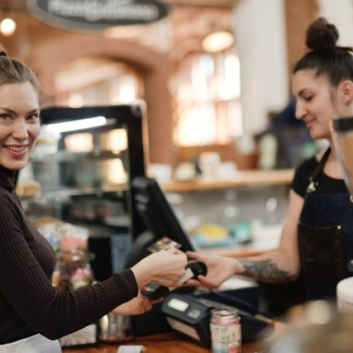 woman-in-black-long-sleeve-shirt-paying-at-a-cashier-3928266
